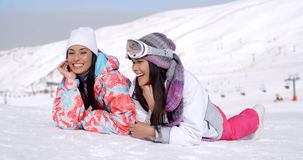 Laughing skiers laying on the ground. Cute pair of female twins in ski clothing laughing while laying down on ground at bottom of ski slope with mountain behind stock video footage