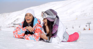 Laughing skiers laying on the ground Royalty Free Stock Photo