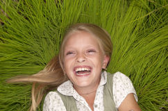 Laughing small girl. In the green grass royalty free stock image