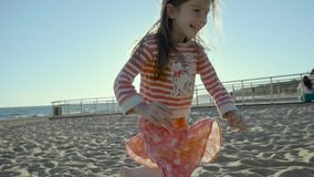 Laughing small girl runs along the sea beach while stumbling into sand in slo-mo. Four year old girl dressed in a striped blouse and red skirt with flowers runs stock video footage
