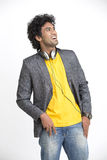 Laughing smart Indian young urban man standing with headphone Stock Photos