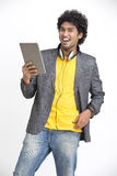 Laughing smart Indian young urban man standing with tablet and  headphone. On white background Stock Photo