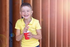 Laughing, smiling boy in yellow shirt standing near wooden wall, holding a red paper cup and drinking through a straw stock image