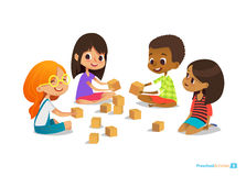 Laughing and smiling kids sit on floor in circle, play with toy cubes talk.