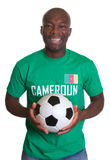 Laughing soccer fan from Cameroon with ball stock photography