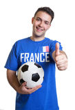 Laughing soccer fan from France with ball showing thumb up Stock Photo