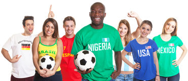 Laughing soccer fan from Nigeria with ball and other fans Royalty Free Stock Images