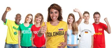 Laughing soccer supporter from Colombia with fans from other countries royalty free stock image