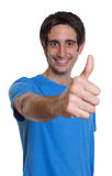 Laughing spanish guy in a blue shirt showing thumb Stock Images