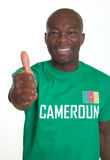 Laughing sports fan from Cameroon showing thumb up. Happy football fan from Cameroon waits for the word cup in Brazil and shows his right thumb up on an isolated Stock Photography