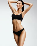 Laughing sporty girl in black bikini posing on grey background. Stock Images