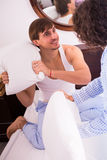 Laughing spouses having pillow fight at home Stock Image