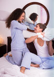 Laughing spouses having pillow fight at home. Laughing husband and young brunette wife having pillow fight royalty free stock image