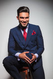 Laughing stilish young man in double breasted suit sitting Royalty Free Stock Image