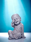 Laughing stone buddah. Close Up image of a laughing stone buddah  on a blue background Royalty Free Stock Photo