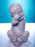 Laughing stone buddah. Close Up image of a laughing stone buddah  on a blue background Stock Photo