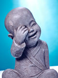 Laughing stone buddah. Close Up image of a laughing stone buddah  on a blue background Stock Image