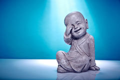 Laughing stone buddah. Close Up image of a laughing stone buddah isolated on a blue background Royalty Free Stock Image