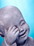 Laughing stone buddah. Close Up image of a laughing stone buddah isolated on a blue background Royalty Free Stock Photography