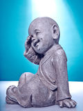 Laughing stone buddah. Close Up image of a laughing stone buddah isolated on a blue background Stock Photos