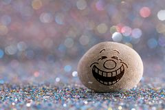 The laughing stone emoji. Emotions on color glitter boke background royalty free stock image