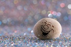The laughing stone emoji. Emotions on color glitter boke background royalty free stock photos