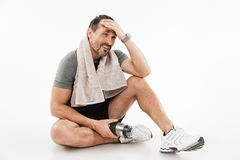Laughing strong mature sportsman sitting with towel and water royalty free stock photo