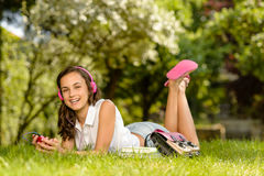 Laughing student girl with headphones lying grass Royalty Free Stock Photos