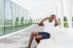Laughing Student with Mobile Phone. Black, African American college student laughing and talking on mobile phone at university campus Royalty Free Stock Image