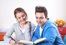 Laughing students reading in a book Royalty Free Stock Images