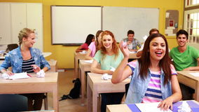 Laughing students throwing paper in classroom stock video footage