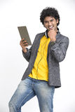 Laughing successful Indian young urban man standing with tablet and  headphone Royalty Free Stock Photos