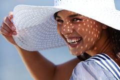 Laughing summer girl. Cheerful girl holding the brim of her hat and laughing at camera in summer royalty free stock photo