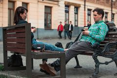 Laughing talking man with woman sitting on bench drinking coffee surfing in internet. urban lifestyle. Laughing talking men with women sitting on bench drinking stock photos