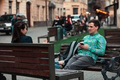 Laughing talking man with woman sitting on bench drinking coffee surfing in internet. urban lifestyle. Laughing talking men with women sitting on bench drinking stock photo