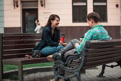 Laughing talking man with woman sitting on bench drinking coffee surfing in internet. urban lifestyle. Laughing talking men with women sitting on bench drinking royalty free stock photo