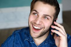 Laughing and talking on mobile phone. Close up portrait of a young man laughing and talking on mobile phone Royalty Free Stock Photos