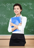 Laughing teacher at the blackboard hands a folder Stock Images