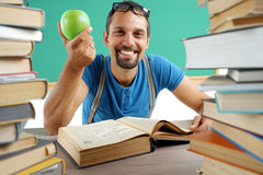 Laughing teacher with open book and holding an apple. Stock Photos