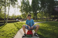 Laughing teen boy sitting on a small toy car in the countryside on a sunny summer evening. In the background there are birch trees royalty free stock photo