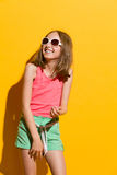 Laughing teen girl. Laughing young summer girl looking away. Three quarter length studio shot on yellow background Royalty Free Stock Photos