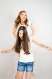 Laughing teen girls jumping. Children laugh and have fun. teen girls 11 years. light background horizontal Stock Photo