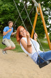 Laughing teenage couple on swing in park Royalty Free Stock Photography