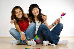 Laughing teenage girls. Two teenage girls laughing and sitting on the floor Stock Photos