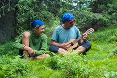 Laughing teenage son and his father in funny sunglasses. Are sitting on a green mountain meadow among huge pine trees, singing and having fun. Joyful moments Stock Image