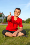 Laughing teenage summer in the grass thumbs up Stock Photos