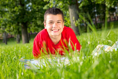 Laughing teenage summer lies in the grass Stock Image