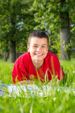 Laughing teenage summer lies in the grass Royalty Free Stock Photo