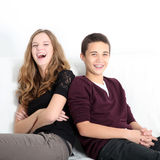 Laughing teenaged brother and sister. Sitting leaning on each other enjoying a good joke, square format with copyspace Royalty Free Stock Photography