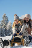 Laughing teenagers sledge downhill in wintertime Royalty Free Stock Photography